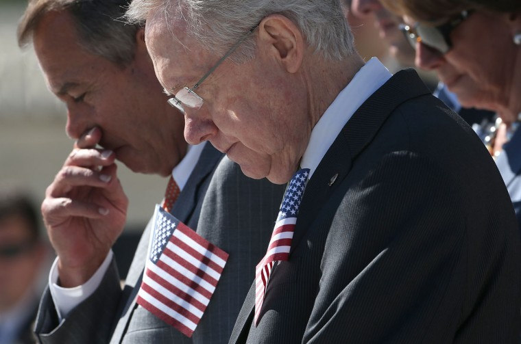 Senate Majority Leader Harry Reid (D-NV) (R) and Speaker of the House John Boehner (R-OH) (L) bow their heads in remembrance of the victims of the attacks of September 11 during a ceremony at the U.S. Capitol September 11, 2012 in Washington, DC. (Win McNamee/Getty Images)