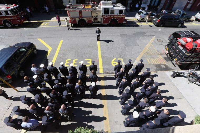 New York City firefighters of Engine 33, Ladder 9 observe a moment of silence during ceremonies for the eleventh anniversary of the terrorist attacks on lower Manhattan at the World Trade Center on September 11, 2012 in New York City. (Mario Tama/Getty Images)