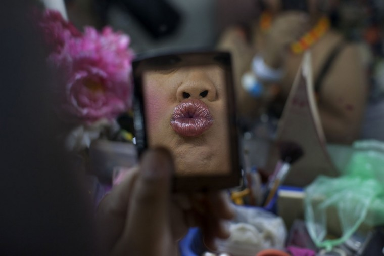 Lily, a ladyboy dancer puts on lipstick backstage as up to 20 dancers get dressed before a performance September 9, 2012 in Chiang Mai, Thailand. The Cabaret show is the only one in Chiang Mai, Thailand's 2nd largest city, performed daily on a stage at a small theater. Kathoeys or ladyboys are very visible, and widely accepted in Thai culture, often called the third gender. Many find employment performing for tourists in Cabaret shows while several popular Thai models, singers and movie stars are also kathoeys. The term Kathoey can refer to males who exhibit varying degrees of femininity most of the kathoeys dress as women and undergo medical procedures such as breast implants, hormones, silicone injections. (Paula Bronstein/Getty Images)
