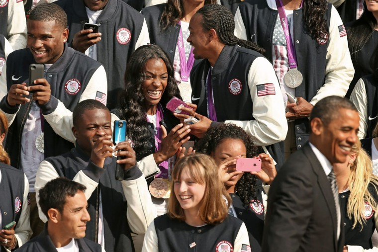 U.S. Olympic and Paralympic team members, including gold medal runner Dee Dee Trotter (center), react to the arrival of U.S. President Barack Obama during an event at the White House. (Chip Somodevilla/Getty Images)