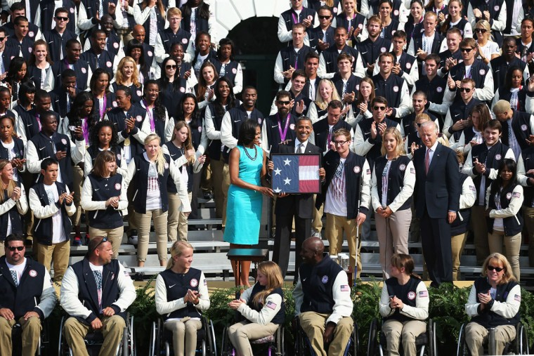 U.S. President Barack Obama, first lady Michelle Obama, Paralympic swimmer Brad Snyder, Olympic fencer Mariel Zagunis, Vice President Joe Biden and members of the U.S. Olympic and Paralympic teams pose for a photograph at the White House. (Chip Somodevilla/Getty Images)