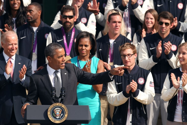 U.S. President Barack Obama addresses members of the 2012 Olympic and Paralympic teams as vice president Joe Biden, first lady Michelle Obama, Paralympic swimmer Brad Snyder (front, second from right), Olympic gold medal swimmer Michael Phelps (back right) and Olympic fencer Mariel Zagunis listen. (Chip Somodevilla/Getty Images)