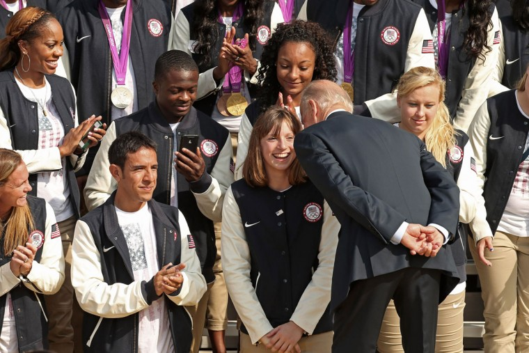 U.S. Vice President Joe Biden whispers to Olympic gold medal swimmer Katie Ledecky, 15, after President Barack Obama commented on her age during a ceremony at the White House. (Chip Somodevilla/Getty Images)
