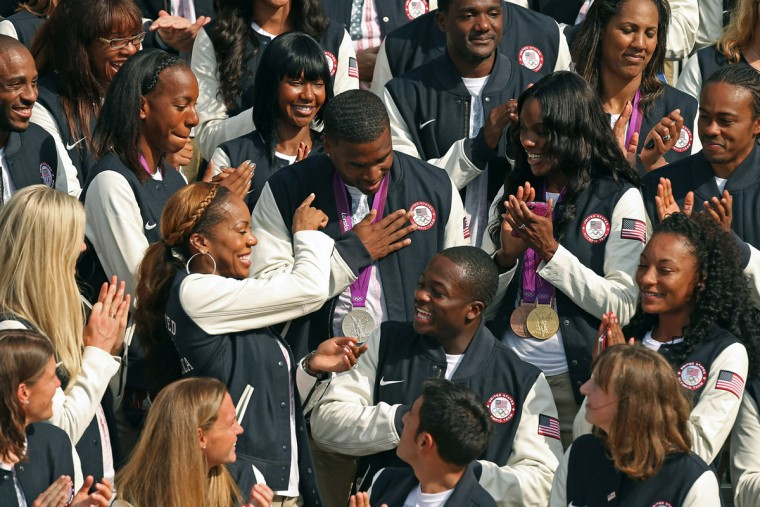 U.S. Olympic sprinter Manteo Mitchell, center, is applauded by his teammates as U.S. President Barack Obama praises his ability to finish a race with a broken leg. (Chip Somodevilla/Getty Images)