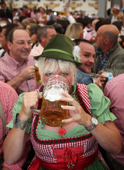 A woman wearing a traditional Bavarian Dirndl dress drinks beer at a beer tent on the opening day of Oktoberfest at Theresienwiese in Munich, Germany. (Alexandra Beier/Getty Images)