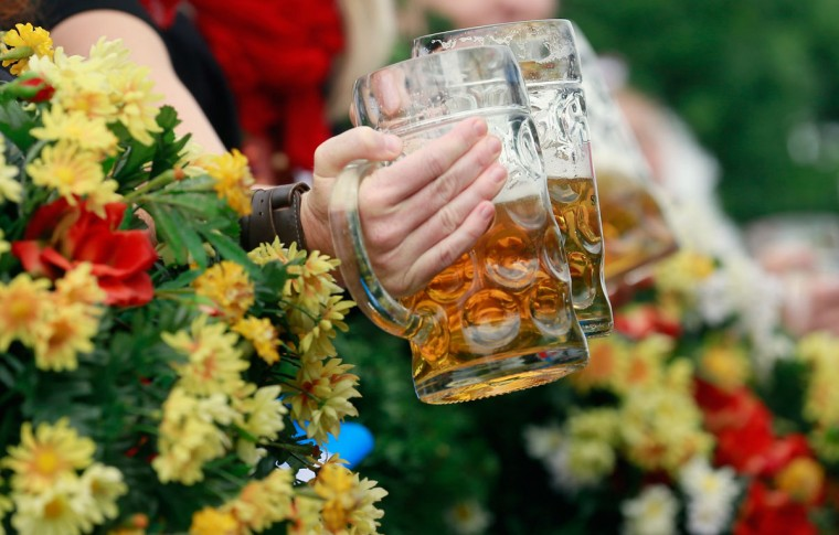 Waitresses of the Spaten brewery wave with beer mugs during the opening parade on the first day of Oktoberfest in Munich, Germany. (Johannes Simon/Getty Images)