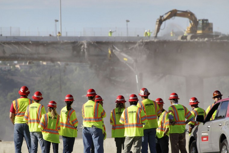 "A group of people monitor construction crews demolishing a portion of the Mulholland Drive bridge along the 405 Freeway in Los Angeles, Calif. The 405 Freeway is completely shut down for the weekend, with Los Angeles residents preparing for a gridlock-filled weekend nicknamed ""Carmageddon 2."" (Jonathan Alcorn/Getty Images)"