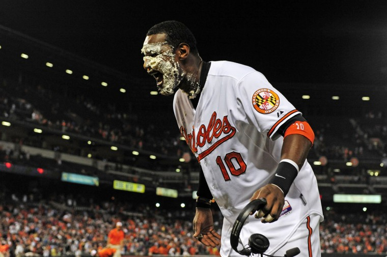August 2014: Adam Jones #10 of the Baltimore Orioles reacts after being hit with a pie after the Orioles defeated the New York Yankees 5-3 during a baseball game at Oriole Park at Camden Yards on August 13, 2014 in Baltimore, MD. (Photo by Patrick McDermott/Getty Images)