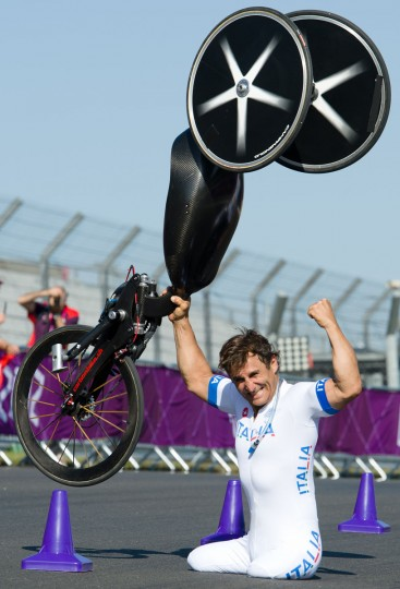 Italy's Alessandro Zanardi holds his bike aloft as he celebrates after winning the gold medal in the men's individual H4 time trial cycling final during the London 2012 Paralympic Games at Brands Hatch circuit, in Kent, southern England on September 5, 2012. (Leon Neal/AFP photo)