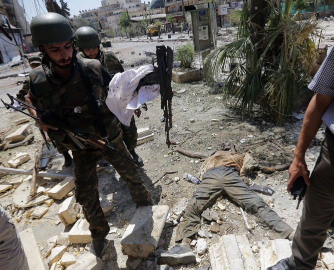 "Syrian Army soldiers carry AK-47 machine guns found next to the bodies of men killed in fighting in the Izaa (Radio) area of the restive Seif al-Dawla neighborhood of northern Syria's main commercial hub Aleppo on September 3, 2012. Syrian troops backed by artillery and warplanes fought rebels on multiple fronts on September 5 as peace envoy Lakhdar Brahimi described the death toll as ""staggering"" and destruction ""catastrophic."" (Joseph Eid/AFP photo)"