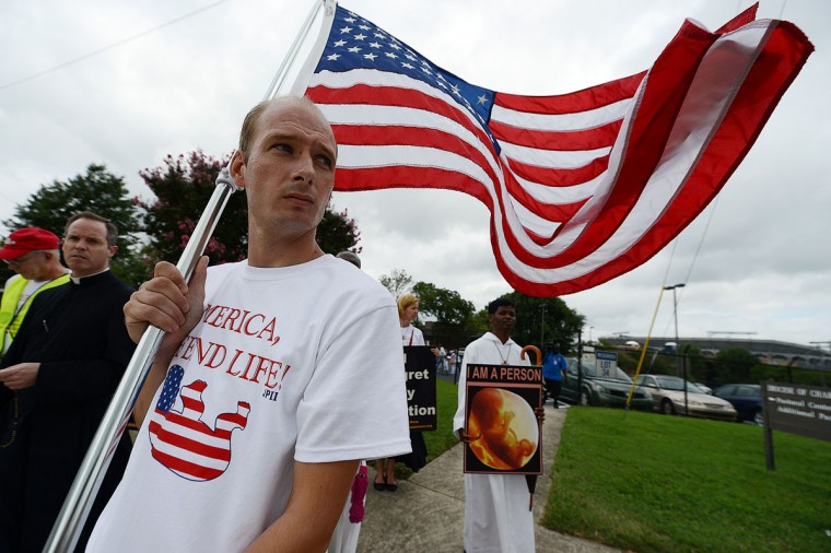 A man holding a US flag leads an anti-abortion rights march and rally on day two of the Democratic National Convention (DNC), in Charlotte, North Carolina. (Robyn Beck/AFP/Getty Images)
