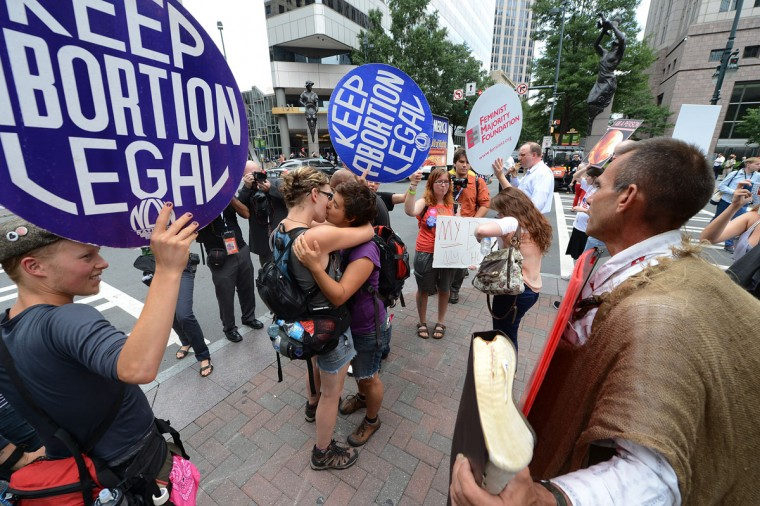 Abortion rights protestors Annah Shapiro (R) and Kat Enyeart (L), two women from Portland, Oregon, kiss in front of street preacher Alan Hoyle (far right) on day two of the Democratic National Convention (DNC), in Charlotte, North Carolina. (Robyn Beck/AFP/Getty Images)