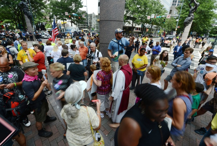 A street preacher in blue shirt on a step ladder holds a bible as he addresses passersby outside the Time Warner Cable Arena on day two of the Democratic National Convention (DNC), in Charlotte, North Carolina. (Robyn Beck/AFP/Getty Images)