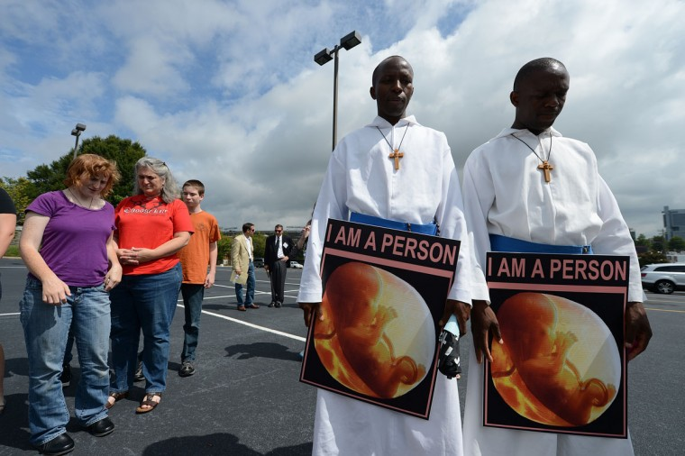 Brother Peter (C) and Brother Pius (R) from Our Lady of Lourdes Catholic Church in Monroe, North Carolina holds signs at an anti-abortion rights march and rally on day two of the Democratic National Convention (DNC), in Charlotte, North Carolina. (Robyn Beck/AFP/Getty Images)