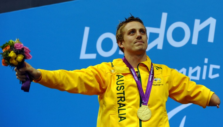 Australia's Matthew Cowdrey stands in the podium wearing his gold medal after winning the men's 50m freestyle S9 final during the swimming competition at the London 2012 Paralympic Games at the Olympic Park Aquatics Centre in east London on September 5, 2012. Cowdrey became Australia's most decorated Paralympian on September 5, smashing his own world record in the S9 50m freestyle as he claimed an historic 11th gold medal. (Paul Ellis/AFP/Getty Images)