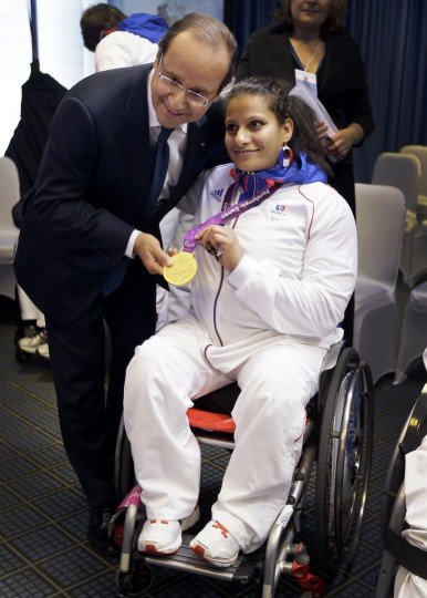 French weightlifter Souhad Ghazouani (R) poses with her gold medal next to French President Francois Hollande after a press conference with French Paralympians in east London on September 6, 2012. (Kristy Wigglesworth/AFP/Getty Images)