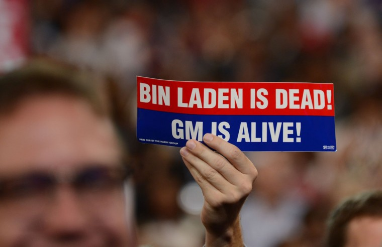 """A man holds up a sign reading """"Bin Laden is dead! GM (General Motors) is alive!) at the Time Warner Cable Arena in Charlotte, North Carolina, on September 6, 2012 on the final day of the Democratic National Convention (DNC). US President Barack Obama is expected to accept the nomination from the DNC to run for a second term as president. (Robyn Beck/AFP photo)"""