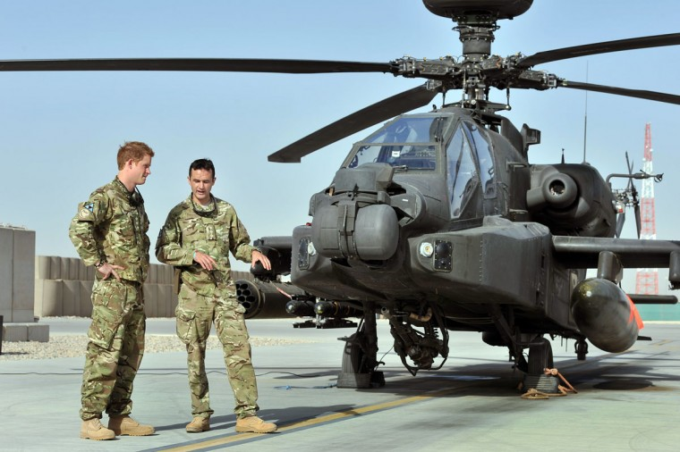 Britain's Prince Harry is shown the Apache flight-line by a member of his squadron at Camp Bastion in Helmand Province, Afghanistan, where he will be operating from during his tour of duty as a co-pilot gunner. Prince Harry is back in Afghanistan to serve as a military helicopter pilot four years after his previous deployment there had to be cut short. (John Stillwell/AFP/Getty Images)