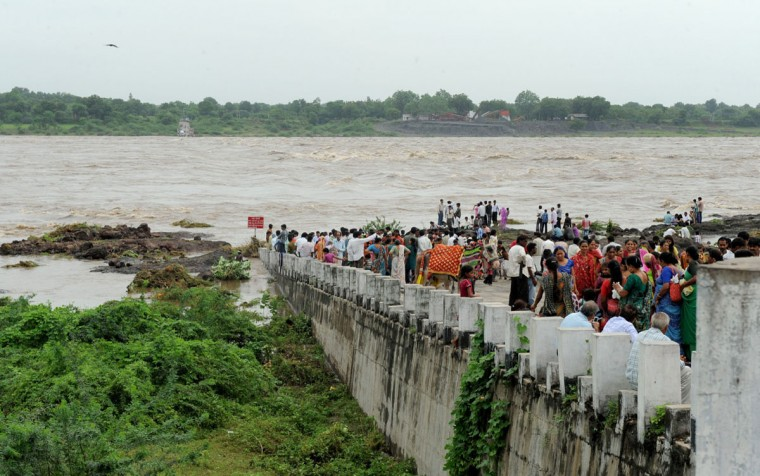 Indian people stand on a submerged bridge on the river Mahisagar at Galteswar village. Thousands of people have been evacuated from many parts of Gujarat owing to heavy delayed monsoon rains. (Sam Panthaky/AFP/Getty Images)
