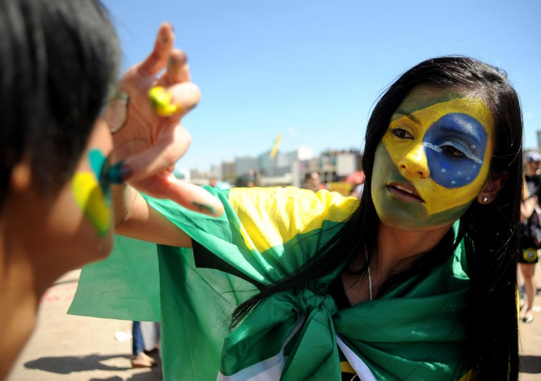 Demonstrators paint their faces with national colors during a demonstration against corruption during Brazil's Independence Day celebration in Brasilia. (Pedro Ladeira/AFP/Getty Images)