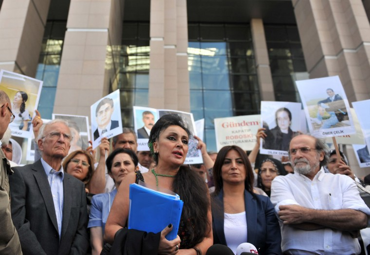 Director of Turkish newspaper Ozgur Gundem, Eren Keskin (C), speaks to the press as Kurdish women hold pictures of jailed journalists in Istanbul on September 10, 2012. Some 44 suspects, 36 of them arrested pending trial, are currently facing charges in the 800-page indictment that was unanimously accepted by the court in May 2012. The suspects are charged with leading a terrorist organization, being a member of a terrorist organization, and being a member of the press committee of a terrorist organization. (Bulent Kilic/AFP/Getty Images)