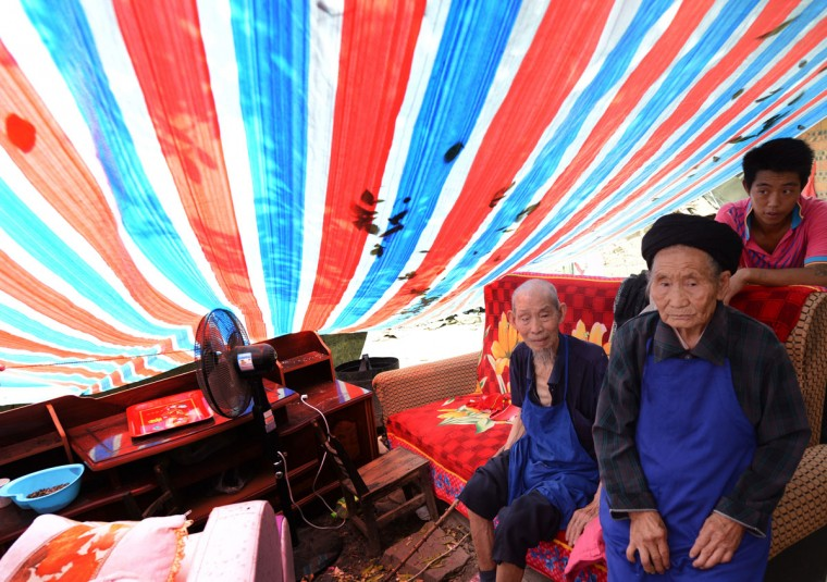 Elderly members of the Peng family sit in their makeshift shelter on September 10, 2012 after their home was badly damaged after a series of earthquakes hit Yiliang County, Yunnan Province on September 7. (Mark Ralston/AFP/Getty Images)