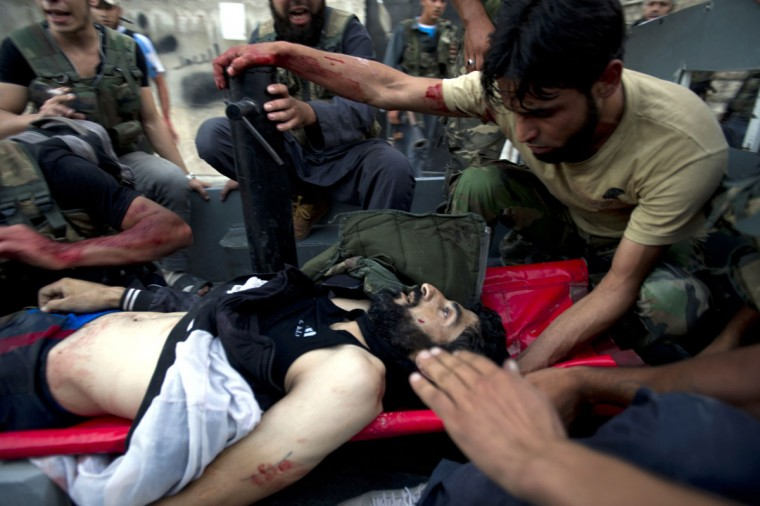 A severely wounded fighter with the Free Syria Army (FSA), who later died from his wounds, is transfered to a hospital during heavy fighting against government forces in Izza neighbourhood of the embattled northern city of Aleppo on September 8, 2012. (Zac Baillie/AFP/Getty Images)