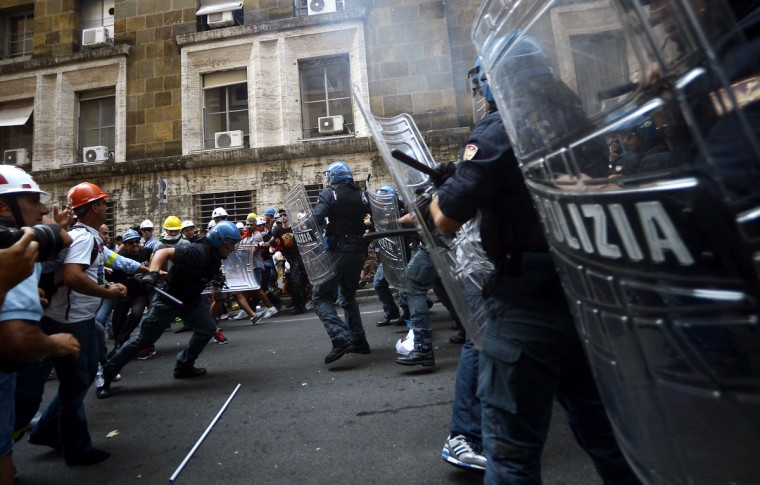 Employees of the world's leading producer of primary aluminum Alcoa, clash with police during a demonstration outside the industry ministry in Rome on September 10, 2012. The demonstrators are protesting the closure of Portovesme and Fusina melting plants on the Italian island of Sardinia, which employ about 2,000 people. (Filippo Monteforte/AFP/Getty Images)
