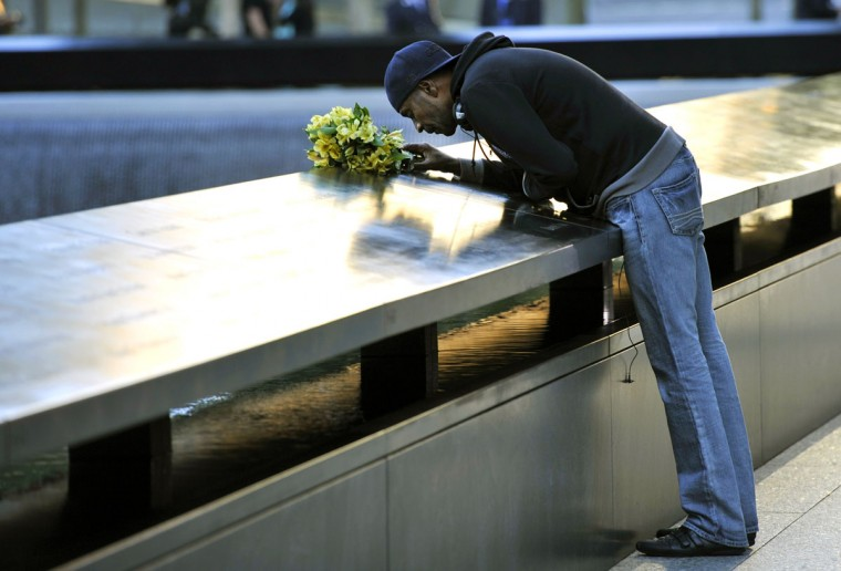 Dennis Swindell kisses the name of his partner Gary Lee Bright on the South Tower pool wall during observances held on the eleventh anniversary of the attacks on the World Trade Center, at the site in New York, September 11, 2012. (Timothy A. Clary/AFP/Getty Images)