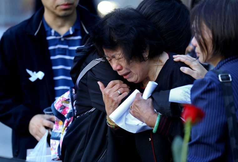 A woman cries as she leans on a friend near the name of Thomas Tong who died in the attacks, at the South Pool wall of the 9/11 Memorial during observances held on the eleventh anniversary of the attacks on the World Trade Center, at the site in New York, September 11, 2012. (Craig Ruttle/AFP/Getty Images)