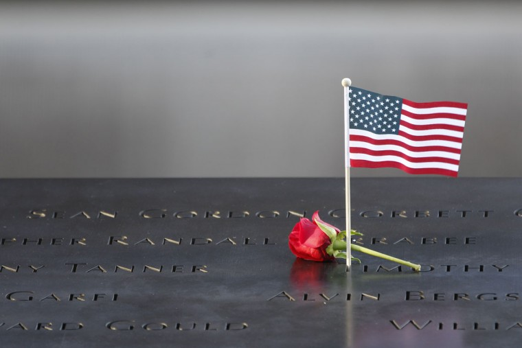 A flower and an American flag are placed next to the names inscribed on the edge of the memorial pool during the observances held on the eleventh anniversary of the attacks on the World Trade Center, September 11, 2012 in New York. (Mary Altaffer-Pool/AFP/Getty Images)