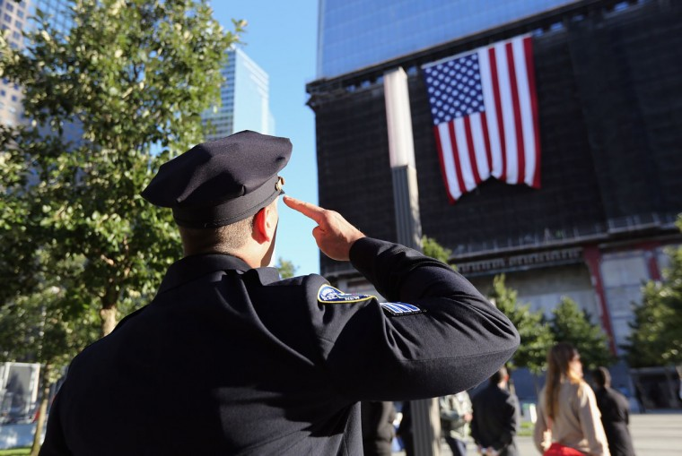 A New York City police officer salutes a flag hanging from One World Trade at ceremonies for the eleventh anniversary of the terrorist attacks on lower Manhattan at the World Trade Center on September 11, 2012 in New York City. (John Moore/AFP/Getty Images)