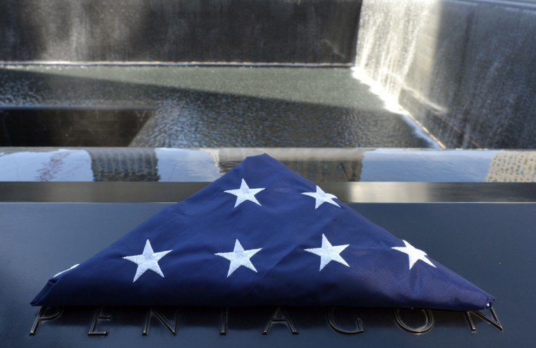 A folded American flag left on the wall near the names of those who died at the Pentagon is seen at the South Tower pool during observances held on the eleventh anniversary of the attacks on the World Trade Center, at the site in New York, September 11, 2012. (Timothy A. Clary/Pool/AFP/Getty Images)