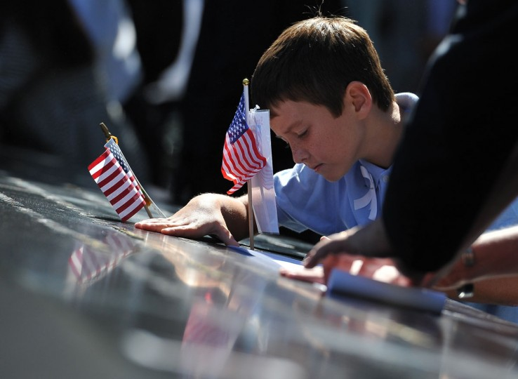 Brian McAleese honors his namesake and uncle, Brian McAleese of Engine Company 226, during observances held on the eleventh anniversary of the attacks on the World Trade Center, at the site in New York, September 11, 2012. (Todd Maisel/pool/AFP/Getty Images)