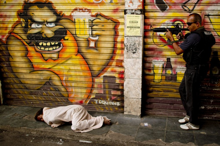 A policeman secures the area before proceeding to pick up a child crack addict sleeping on the sidewalk at the entrance of the Jacare shantytown during an operation to clean the streets of crack addicts, in Rio de Janeiro, Brazil on September 12, 2012.(Christophe Simon/AFP/Getty Images)