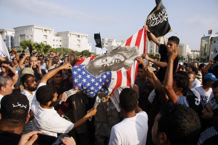 "Tunisian protesters burn a US flag bearing a portrait of US actress Marilyn Monroe during a demonstration against a film deemed offensive to Islam, outside the US embassy in Tunis. A purported portrayal of the life of the Prophet Mohammed in the low-budget ""Innocence of Muslims"" movie sparked protests in Egypt and violence in Libya that killed US ambassador Chris Stevens and three American officials. (Getty Images)"