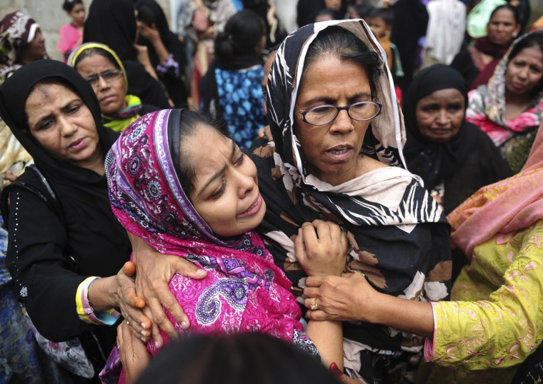 Relatives mourn the death of a loved one during a funeral for a garment factory victim in Karachi. Pakistan on September 13 registered murder charges against factory bosses and government officials over the deaths of 289 people in the country's worst industrial disaster, police said. (Asif Hassan/GettyImages)