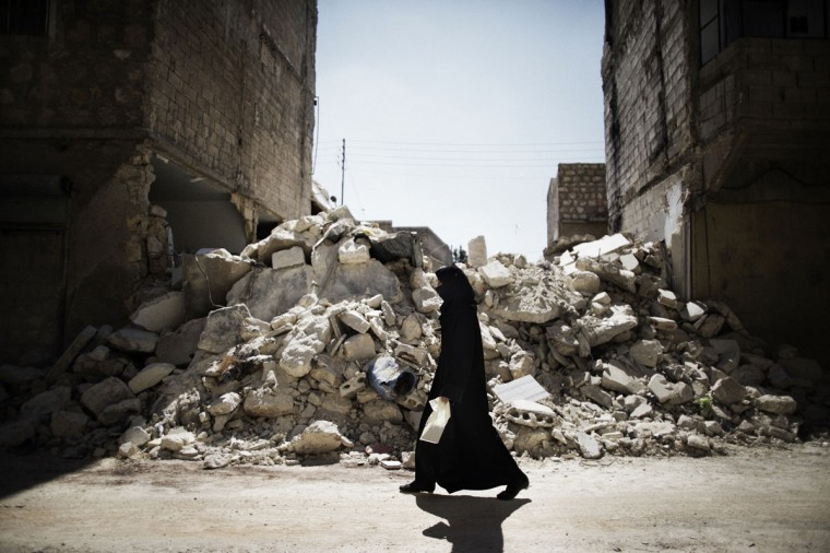 A Syrian woman walks past a destroyed building while reaching a food distribution centre in Aleppo on September 13, 2012. Syrian fighter jets and tanks pounded the northern city of Aleppo, an AFP journalist said, as witnesses reported rebels advancing into the key contested central Midan district. (Marco Longari/AFP/Getty Images)