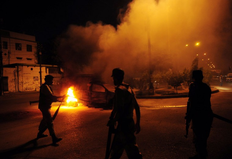 Pakistani paramilitary soldiers stand near a burning police van during a protest rally organised by Pakistani Shiite Muslims against an American produced film mocking Islam on September 16, 2012 in Karachi. (Arif Ali/AFP/Getty Images)