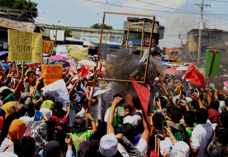 """Philippine Muslims burn U.S. and Israeli flags attached to a tarpaulin during a protest against an anti-Islam film, in Marawi City, Lanao del sur province, in southern island of Mindanao on September 17, 2012. The low-budget movie, entitled """"Innocence of Muslims"""", has sparked fury across the Islamic world for mocking the Prophet Mohammed, and for portraying Muslims as immoral and gratuitously violent. (Richel Umel/AFP/Getty Images)-"""