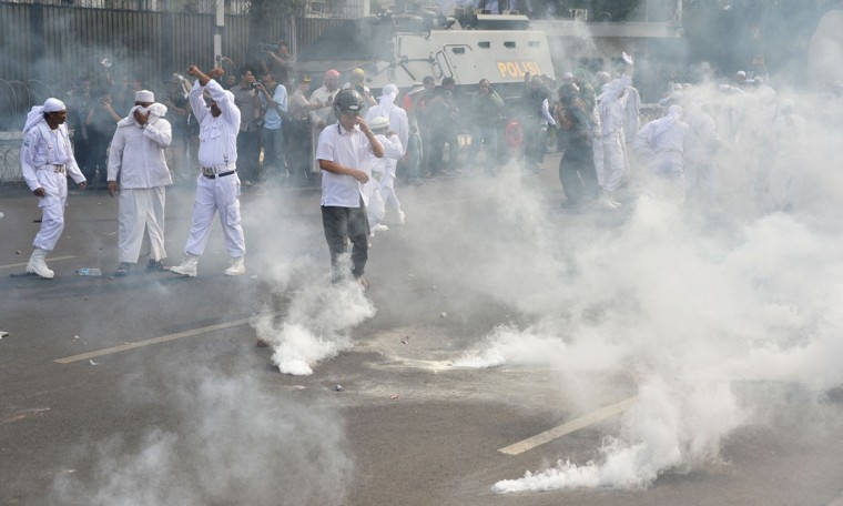 Indonesian Muslim protesters disperse as anti-riot police launch tear-gas shots during a protest against a low-budget film insulting to Muslims outside the U.S. embassy in Jakarta on September 17, 2012. (Adek Berry/AFP/Getty Images)