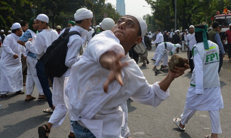 An Indonesian Muslim protester hurls a rock during a protest against a low-budget film insulting to Muslims outside the U.S. embassy in Jakarta on September 17, 2012. Protesters hurled petrol bombs and clashed with Indonesian police outside the U.S. Embassy in Jakarta on September 17, as demonstrations in the world's most populous Muslim nation turned violent. (Adek Berry/AFP/Getty Images)