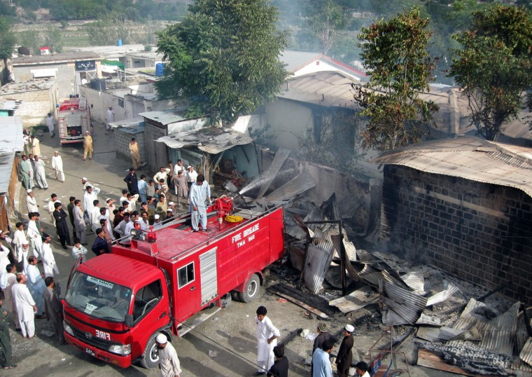 "Pakistani firefighters cool down burning government offices following a protest rally organised by Pakistani Muslims against an anti-Islam movie in the northwestern town of Warai, in Upper Dir district on September 17, 2012. Two protesters died in Pakistan as a violent backlash against a US film mocking Islam spread across the region and angry demonstrators clashed with police, hurled stones and shouted ""Death to America."" (Ihsan Ullah/AFP/Getty Images)"