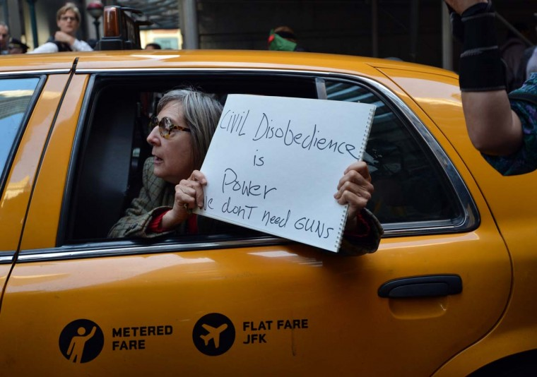 A woman in a taxi holds a sign as Occupy Wall Street protesters pass by on the one year anniversary of the movement in New York. (Stan Honda/Getty Images)