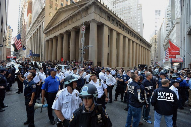 Occupy Wall Street protesters and New York City Police Department officers block an intersection near Wall Street September 17, 2012 on the one year an
