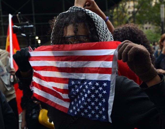 An Occupy Wall Street protester holds an American flag upside down as a sign of distress near Wall Street on the one year anniversary of the movement in New York. (Stan Honda/Getty Images)