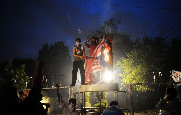 Pakistani Shiite Muslims torch a US flag in front of the US consulate building during a protest against an anti-Islam movie in Lahore on September 17, 2012. (Arif Ali/AFP/Getty Images)