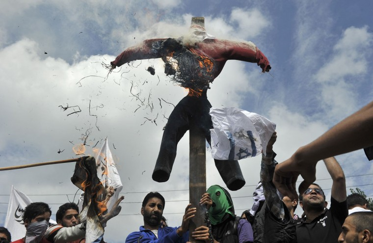 Kashmiri Muslims burn an effigy representing the US during a protest and one day strike called by several religious and political organisations to protest an anti-Islam movie in Srinagar. Protestors rallied in Kashmir over an anti-Islam film, taking to the streets and burning US and Israeli flags and an effigy of US President Barack Obama. (Tauseef Mustafa/AFP/Getty Images)
