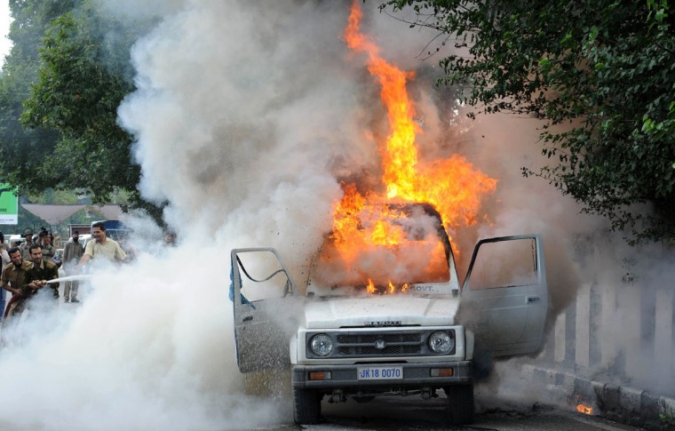 Firefighters attempt to extinguish the flames in an Indian police vehicle burning as protesters clash with police during a protest and one day strike called by several religious and political organisations to protest an anti-Islam movie in Srinagar on September 18, 2012. (Rouf Bhat/AFP/Getty Images)