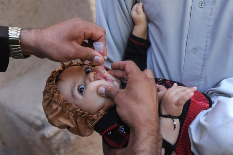 An Afghan health worker (L) administers a polio vaccination to a child on the third day of a vaccination campaign in Herat. A new three-day nationwide immunization campaign against polio began on September 16 in all over the country. (Aref KarimiAref Karimi/AFP/Getty Images)